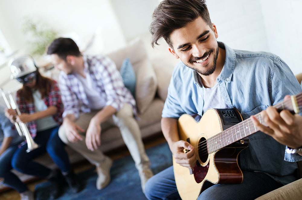 Man Playing Guitar With Friends